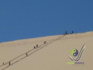 Climbing to the  300 m high Singing Dune