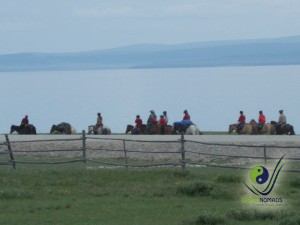 Horse riders by the lake shore